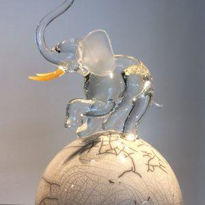 Verrerie d'art animalière - Eléphant trompe levée sculpté en verre translucide sur une sphère blanche en raku - Collaboration Art Verrier - Maud Lelièvre